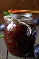 marmellata di prugne in un barattolo trasparente e un cucchiaio di legno foto