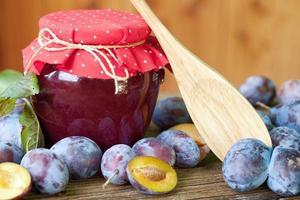 marmellata di prugne con frutta fresca su fondo di legno foto