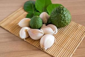 bergamotto e aglio sulla stuoia di makisu su struttura di legno foto