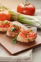 Bruschetta italiana con pomodori cipolla e basilico foto