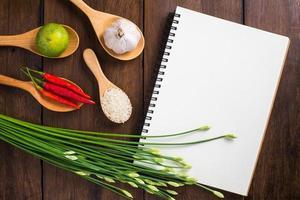 taccuino di ricette, riso, peperoncino rosso, aglio e limone su legno