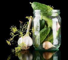 i cetrioli in barattolo si preparano per la conservazione sul nero foto