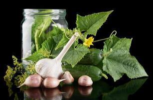 i cetrioli in barattolo preparano il decapaggio sul nero foto