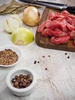 fette di carne cruda sul tagliere con pepe e cipolla foto