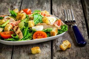 insalata caesar con crostini, uova di quaglia, pomodori e pollo alla griglia