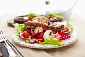 pollo e salsiccia a dadini arrostiti con insalata di pomodori