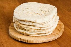 pila di pane pita sul piatto di legno al tavolo foto