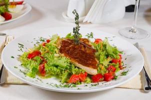 deliziosa ricetta su lattuga frisee sul piatto bianco foto