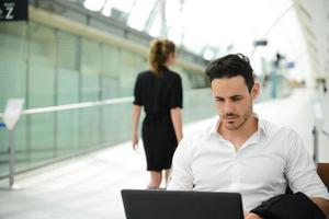 stazione pubblica del giovane uomo d'affari bello con il computer nell'area di wifi foto