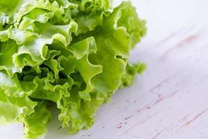 insalata di lattuga, fondo di legno bianco foto