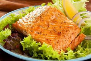 salmone fresco su un mucchio di lattuga foto