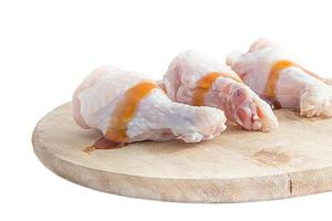 cosce di pollo crude su taglieri di legno su sfondo bianco foto