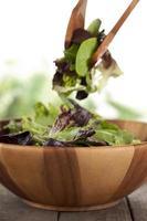 mescolando le verdure sulla ciotola di legno foto