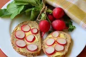 mazzo di ravanelli con pane ai cereali sul piatto bianco foto