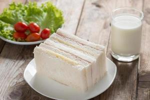 panino, prosciutto con formaggio e latte sul tavolo di legno. foto