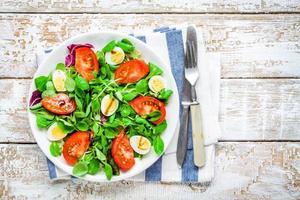 insalata verde fresca con lattuga di agnello, pomodori e uova di quaglia
