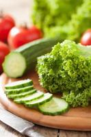 pomodori freschi del cetriolo e foglie dell'insalata sul tagliere
