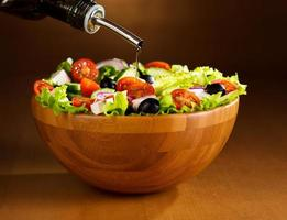 olio versando nella ciotola di insalata di verdure foto