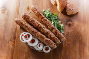 kebab di lula con erbe su una superficie di legno foto
