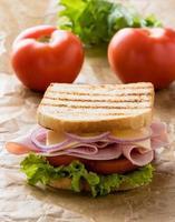 toast prosciutto sandwich su carta marrone foto