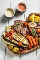 bistecca arrosto e verdure con erbe su tavola di legno