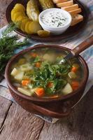 zuppa di cetriolo polacco sul primo piano tavolo. verticale foto