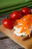 fetta di pane con formaggio fresco e scaglie di carota foto