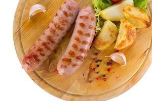 gustose salsicce alla griglia su tavola di legno foto