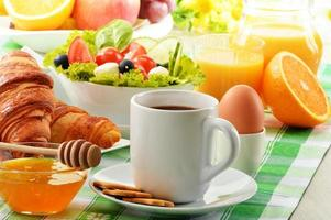 colazione con caffè, succo d'arancia, cornetto, uovo, verdure