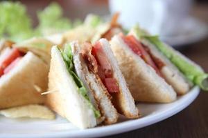 club sandwich con caffè su fondo di legno foto