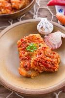 pesce di tipo greco con verdure e salsa di pomodoro