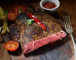 bistecca sullo sfondo in legno con verdure arrosto foto