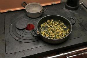 zucchine verdi con pentola sul fornello in montagna foto