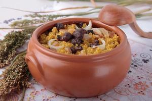 pentola di porridge di miglio con porcini, cipolle e pancetta foto