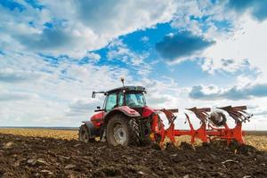 agricoltore che ara campo in trattore da equitazione rosso
