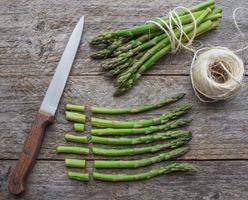 asparagi verdi maturi su uno sfondo di legno foto