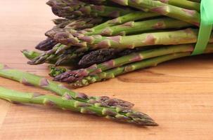 asparagi verdi su superficie di legno, alimentazione sana foto