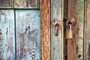 vicino dettaglio di lucchetto e vecchia porta di legno foto