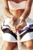 la donna passa la tenuta della sabbia sulla spiaggia foto