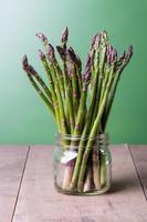asparagi verdi freschi in un barattolo di vetro foto