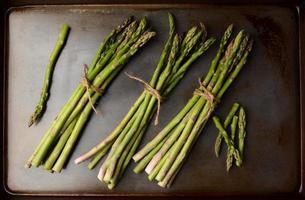 grappoli di asparagi sul foglio di cottura foto