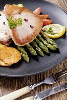 bistecca di tonno alla griglia servita su asparagi con zmieniakami arrosto foto