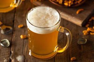 birra dorata in un boccale di vetro foto