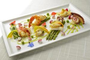 piatto di pesce brasato gamberi aragosta capesante calamari polpo asparagi foto