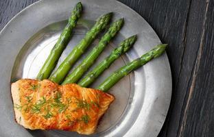 filetto di salmone con asparagi sul vecchio piatto di latta