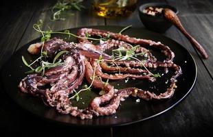 calamari freschi con asparagi su un piatto nero foto