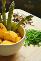 asparagi e barbabietole dorate sul tagliere di bambù e tazza foto