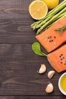 filetto di salmone fresco con spezie su fondo in legno foto