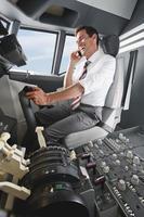 uomo d'affari guida aeroplano in cabina di guida e utilizzando il telefono cellulare foto