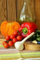 pomodori e peperoni maturi su una lavagna.